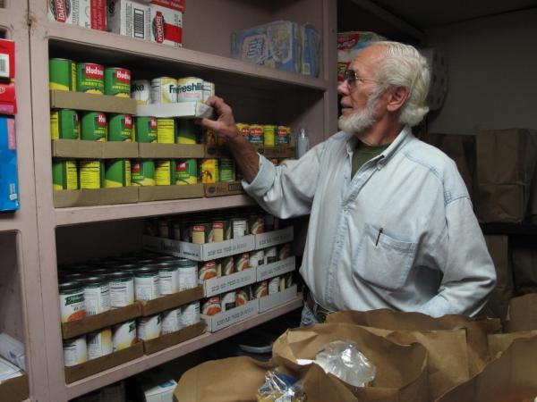 <p>Volunteer Dean Ford prepares bags of food to be distributed at the First Baptist Spartanburg's food pantry program. </p>