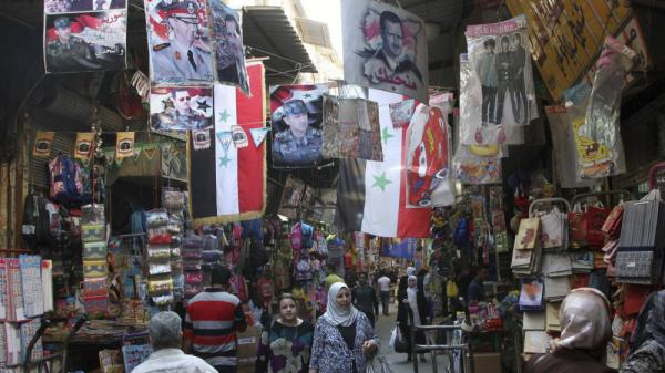 <p>Syrians walk in the Hamidiyah market, decorated with portraits of Syrian President Bashar Assad and Syrian flags, in Damascus, Syria, Oct. 5, 2011. The European Union has intensified economic sanctions against Syria, but the crackdown against anti-regime protesters is unlikely to stop, Syrians say.</p>