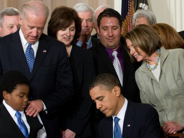 <p>President Obama, surrounded by lawmakers and guests, signs health care insurance legislation during a ceremony in the East Room of the White House on March 23, 2010. </p>