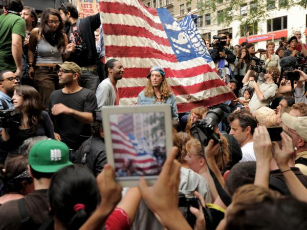 <p>An onlooker takes a photograph of Occupy Wall Street protesters in New York's Zuccotti Park. The demonstrations were inspired by a blog post by Kalle Lasn, editor of <em>Adbusters</em> magazine.</p>