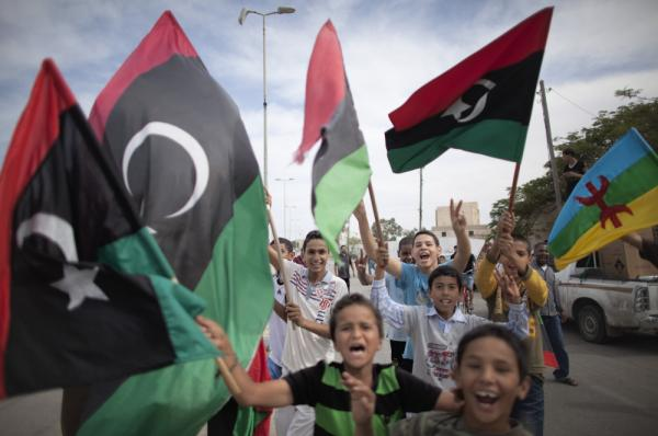 <p>Libyan children waving National Transitional Council (NTC) flags celebrate in the streets of Tripoli following news of Moammar Gadhafi's death.</p>
