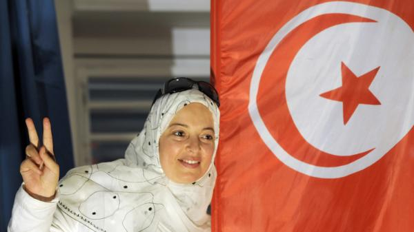 <p>A supporter of Tunisia's Islamist Ennahda party celebrates on Tuesday at the party's headquarters in Tunis. Ennahda is leading the results of Tunisia's first free and democratic election — though is not expected to win an outright majority.</p>