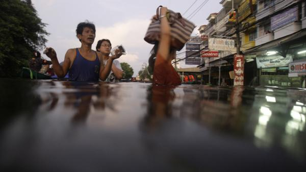 <p>Residents wade along a flooded street on the outskirts of Bangkok Thursday. Clambering aboard bamboo rafts and army trucks, residents fled their homes as high waters moved closer to the heart of the city. </p>
