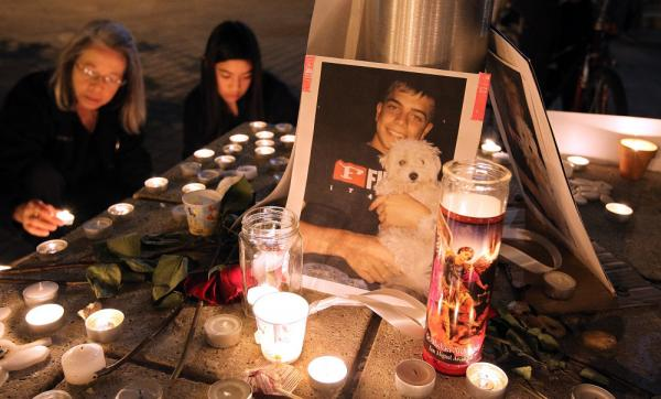 <p>A photograph of Iraq War veteran Scott Olsen is seen Thursday at a vigil. Olsen was severely injured during a standoff between police and protesters in Oakland, Calif., two days earlier. He remains hospitalized.</p>