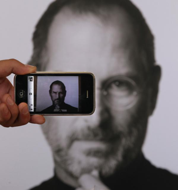 <p>A photographer uses his iPhone to take a picture of a tribute to Apple co-founder Steve Jobs in front of an Apple store in London. </p>