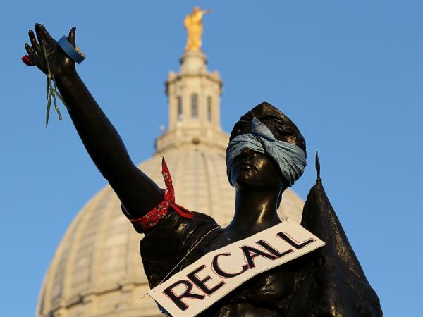 "<p>A sign that reads ""recall"" hangs on a statue in front of the Wisconsin state Capitol last month in Madison. Labor groups are making an effort to recall Gov. Scott Walker for his controversial union rights law.</p>"