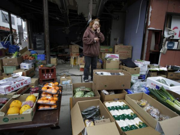 Vegetable shop clerk Emi Akiyama talks on a cellphone in Kesennuma in May. The Japanese government has proposed surrounding all coastal towns with 20-foot tsunami barriers, but residents of Kesennuma, who are trying to boost tourism, have decided not to do so.
