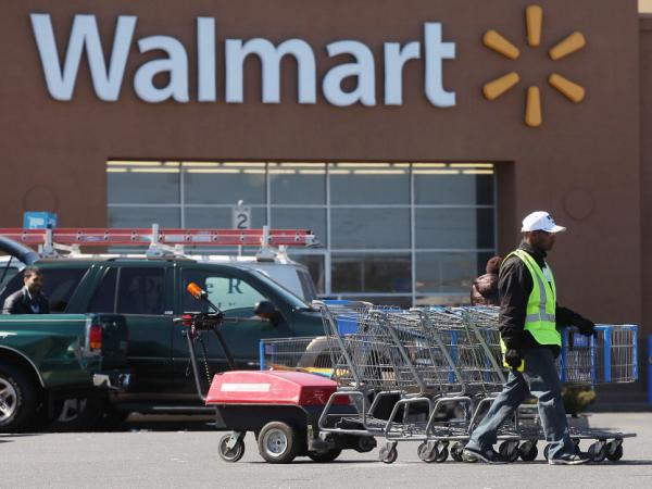 A man pushes carriages outside a Walmart store in Valley Stream, N.Y., early this year. The company is scaling back on health benefits for part-time workers.