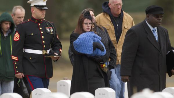Kait Wyatt carries her 1-month-old son, Michael, at the burial for her husband, Marine Cpl. Derek Wyatt, at Arlington National Cemetery, Jan. 7. Wyatt was killed Dec. 6, 2010, in Afghanistan. Kait Wyatt, who was pregnant at the time of her husband's death, was induced the day after he was killed so she could attend the service.