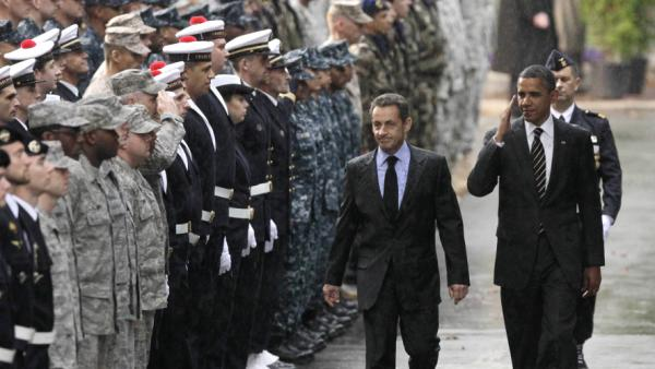 President Obama salutes service members from both sides of the Atlantic as he walks with French President Nicolas Sarkozy during the G-20 summit in Cannes, France, last week.