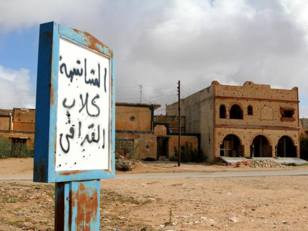 "A sign in the abandoned village near Zintan reads, ""Mushashya: Gadhafi dogs."""