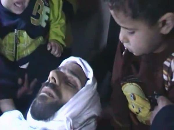 A frame grab from a video posted on YouTube on November 4, shows two young boys sitting next to the body of a dead man identified as Yahya Hamad from Baba Amer neighborhood in Homs, where a rights watchdog has said that several victims were killed by Syrian security forces despite a Damascus pledge to withdraw forces from protest hubs.