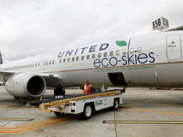 Employees load bags onto a Boeing 737-800 running on algae-based biofuel in Houston. Continental (owned by United Continental Holdings Inc.) flew the nation's first passenger jet powered by biofuels on Monday.