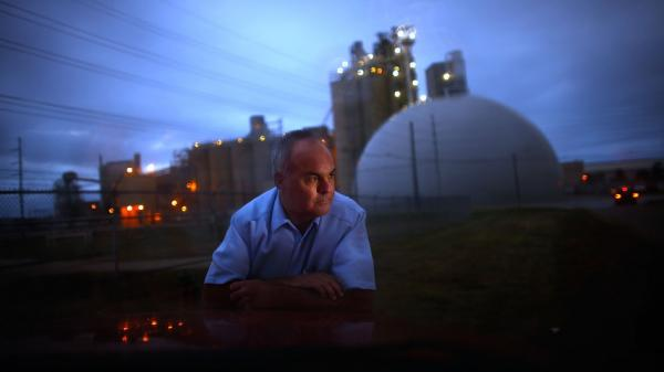 Jeff Galemore leans on his pickup truck near the Ash Grove Cement plant in Chanute, Kan. He and his family are concerned about the toxic emissions and are fighting for independent testing downwind.