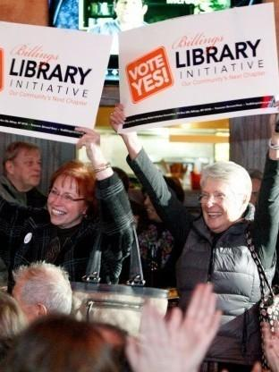 Billings Library Foundation Board President Evelyn Noennig (left) and Suzanne McKiernan arrive at a bar carrying signs to support an initiative for a library bond, as patrons gathered to watch election results.