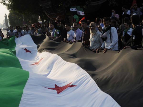 Pro-democracy protesters, holding a huge pre-Baath era Syrian flag outside the Arab league headquarters in Cairo on November 2, 2011.