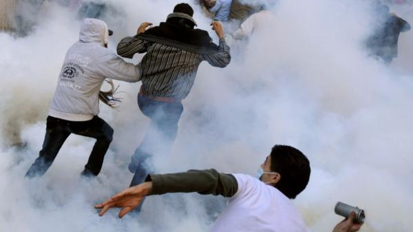A protester in Cairo's Tahrir Square prepared to hurl a tear gas canister at Egyptian security forces as others ran for cover Monday.