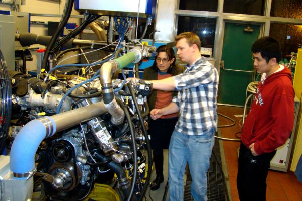 Professor Anna Stefanopoulou (left) examines an internal combustion engine test with engineers Jacob Larimore and Xinfan Lin at the University of Michigan's Automotive Research Center. The researchers model engine performance to improve efficiency.