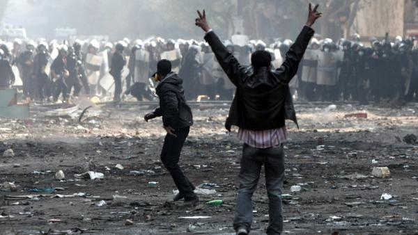 An Egyptian protester flashes the victory sign during clashes with riot police near Cairo's Tahrir Square on Wednesday. The clashes in recent days have clouded Egypt's future as it prepares for elections on Monday.