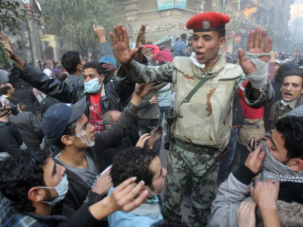 An Egyptian soldier tries to calm protesters during demonstrations Tuesday in Cairo's Tahrir Square. The protesters are demanding an end to military rule.