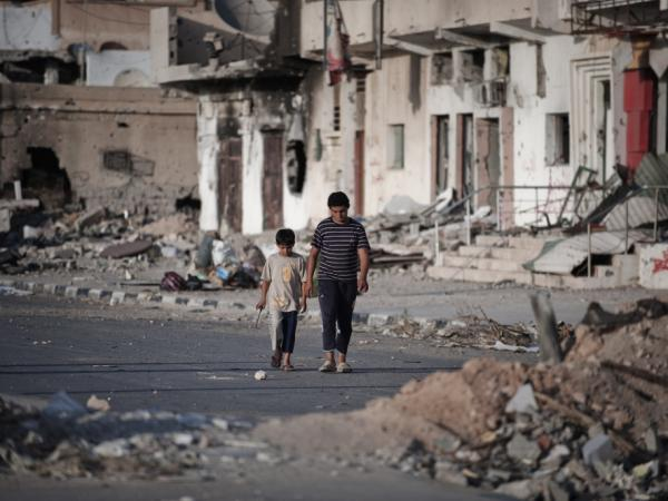Two Libyan children walk through the debris and rubble of Tripoli street on July 1 in the Libyan port city of Misrata, the third largest city in Libya.