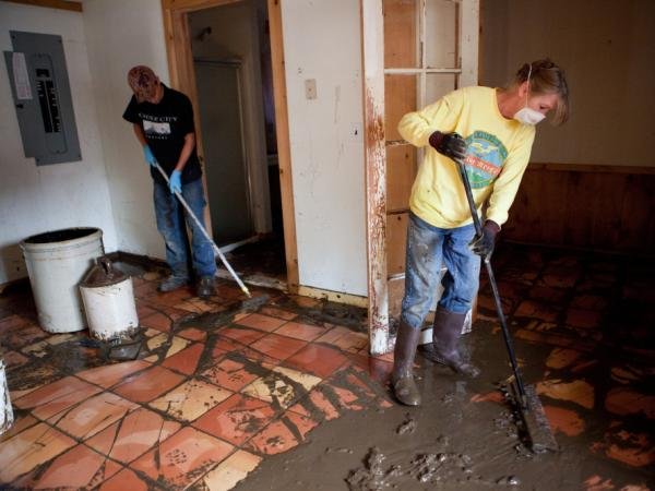 Joyce Roy (right) and Oscar Smith clean up mud from flooding caused by Tropical Storm Irene, in an apartment on West Main Street last month in Wilmington, Vt.  The nearby Deerfield River overflowed its banks a few days earlier, inundating homes and businesses in the downtown area.