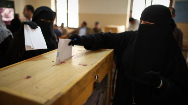 Nov. 28: Women place their votes in a ballot box at a polling station in a girls school in Cairo.