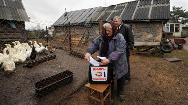 A Russian woman votes Sunday at a mobile ballot box in the western village of Shelomets. Prime Minister Vladimir Putin's United Russia party received around half the vote and will control the next parliament, but its majority was significantly reduced.