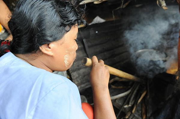 Fuel-efficient stoves use significantly less firewood than a traditional three-stone stove. This woman in Myanmar is using a pipe to help increase the fire's flames to cook the food. Photo by Benny Manser/Mercy Corps