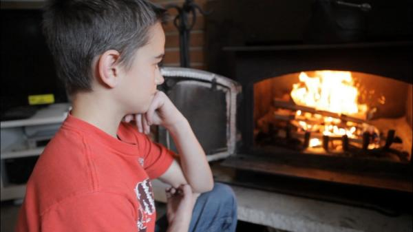 Alex Smith, 13, admires the fire he built in his family's wood stove in Puyallup.