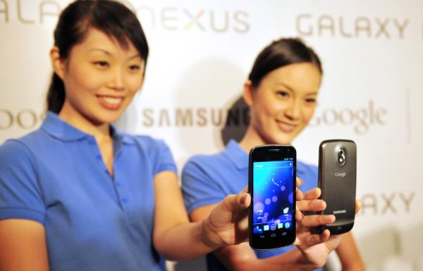 "Models hold the new Samsung Galaxy Nexus Android phone during its official launch in Hong Kong in October. The new smartphone runs Google's Android ""Ice Cream Sandwich"" operating system."