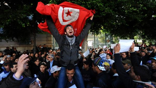 Tunisians protest outside the gates to the French embassy in Tunis. The country is where the Arab Spring began when a fruit vendor set himself on fire in protest in front of a government building.
