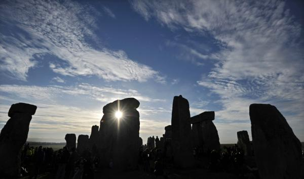 The sun rises behind Stonehenge as revellers celebrate the pagan festival of 'Summer Solstice' in 2010.
