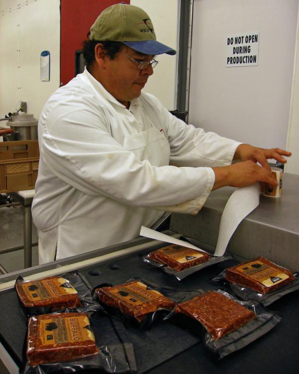 Shane Brown, a butcher with the Wild Idea Buffalo Company, labels packages of ground bison.