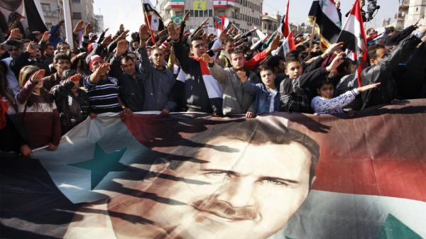 Critics of Syrian President Bashar Assad have been debating whether it would be better to threaten him with prosecution or encourage him to go into exile. Here, Syrians hold a rally supporting Assad in Damascus this month.
