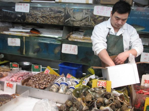 A vendor sells seafood at a market in East Broadway in New York City's Chinatown. There was a 17 percent drop in the population of New York City's Chinatown over the past decade, and some say it's a sign that Chinatown is becoming more of a symbolic touchstone.