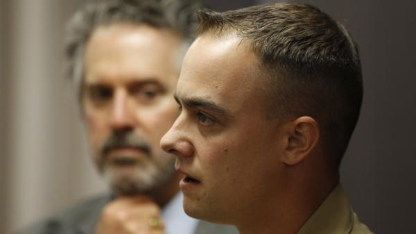 Marine Staff Sgt. Frank Wuterich talks to the media with his attorney Neal Puckett (left) watching on after a 2010 pretrial hearing at Camp Pendleton in California. Wuterich is charged with voluntary manslaughter in the deaths of 24 Iraqi civilians in 2005.