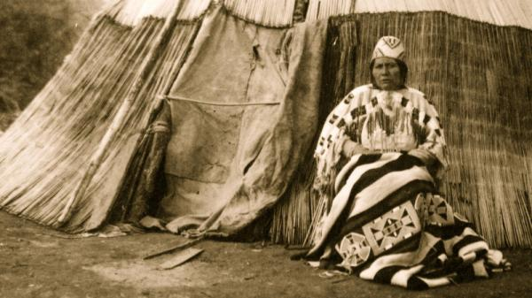 Edna Kash-kash, a Native American from Oregon, sits in front of a tepee circa 1900. In Eastern Oregon, a tribal celebration of first foods offers a connection to ancestors.