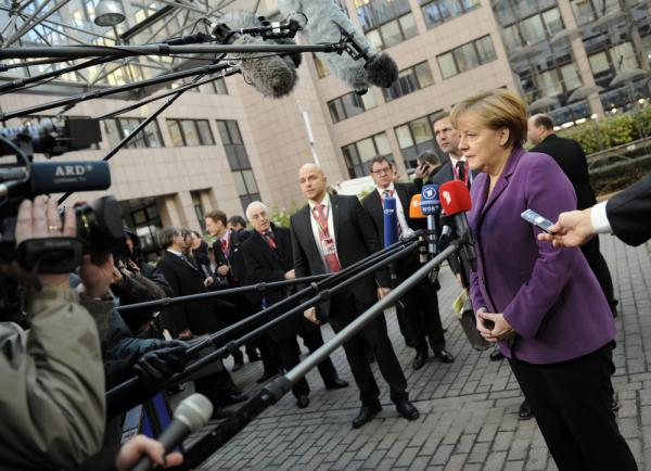 German Chancellor Angela Merkel addresses journalists at EU headquarters in Brussels in December. It's possible that European leaders will come up with ways to manage the region's debt crisis in the new year, but the worst case scenarios are dire.