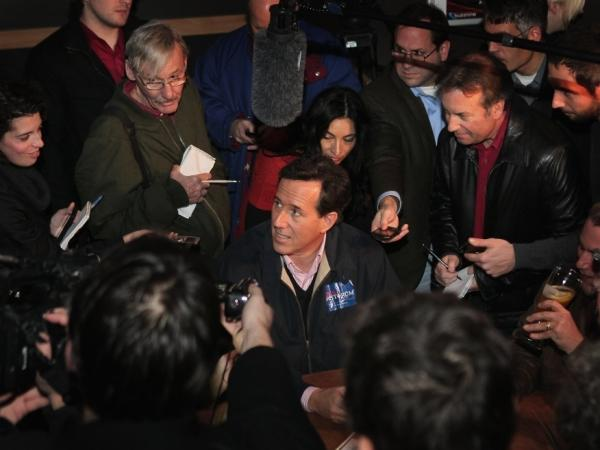 Republican presidential candidate and former U.S. Senator Rick Santorum (R-PA) is mobbed by press while hosting a Pinstripe Bowl watch party at Buffalo Wild Wings Grill and Bar on Dec. 30, 2011 in Ames, Iowa.