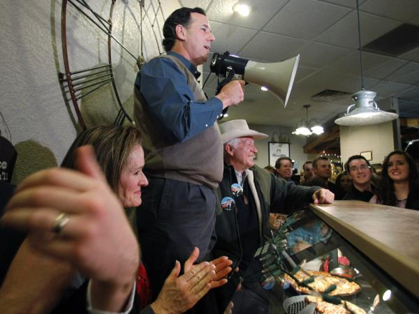Former Pennsylvania Sen. Rick Santorum, who has recently surged in the Iowa polls, used a bull horn during a meet-and-greet campaign stop Monday at the Pizza Ranch in Altoona, Iowa.