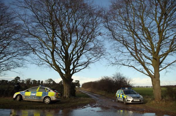 Police guard the entrance to woods on Kings Avenue where human remains were found on New Year's Day in King's Lynn, England.