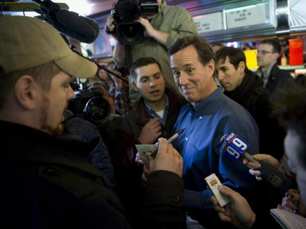 Former Pennsylvania Senator Rick Santorum talks with a customer while surrounded by news crews as he pays a visit to customers at the Tilt 'n Diner in Tilton, NH, on Jan. 5.