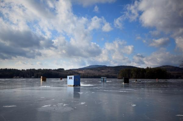Fishing shelters perch on top of the recently frozen ice at Highland Lake in Andover, N.H.