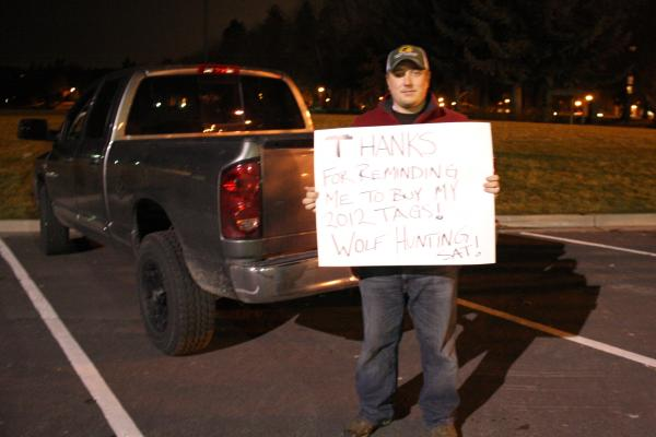 "Patrick Krapfl of Coeur d'Alene holds a sign saying ""Thanks for reminding me to buy my 2012 tags!"" He joined other hunters in a counter protest of the wolf vigil. By Jessica Robinson."