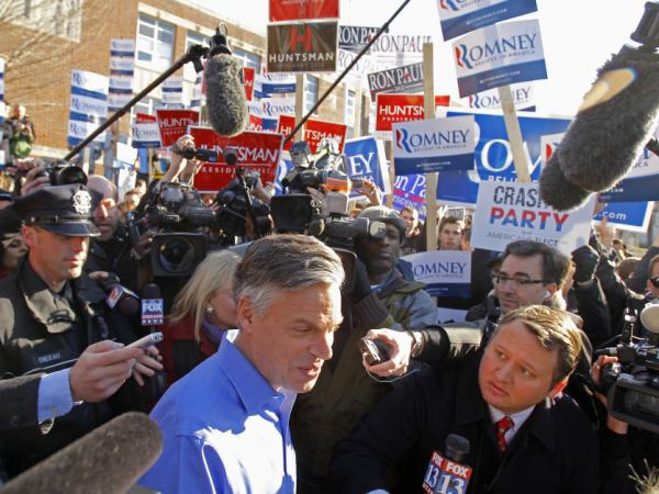 Former Utah Gov. Jon Huntsman makes his way through the media as he leaves a polling station in Manchester, N.H. on Jan. 10. He's one of the candidates two young Mormons are often asked about as they proselytize.
