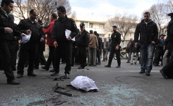 Iranian security forces inspect the site where a magnetic bomb attached to a car by a motorcyclist exploded outside a university in Tehran on Jan. 11, 2012, killing nuclear scientist Mostafa Ahmadi Roshan.