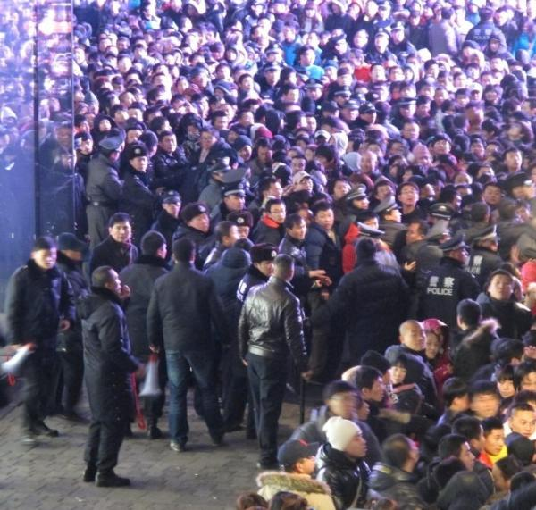 Police tried to seal off the area as thousands of customers gathered outside an Apple store in Beijing's upmarket Sanlitun shopping district today.