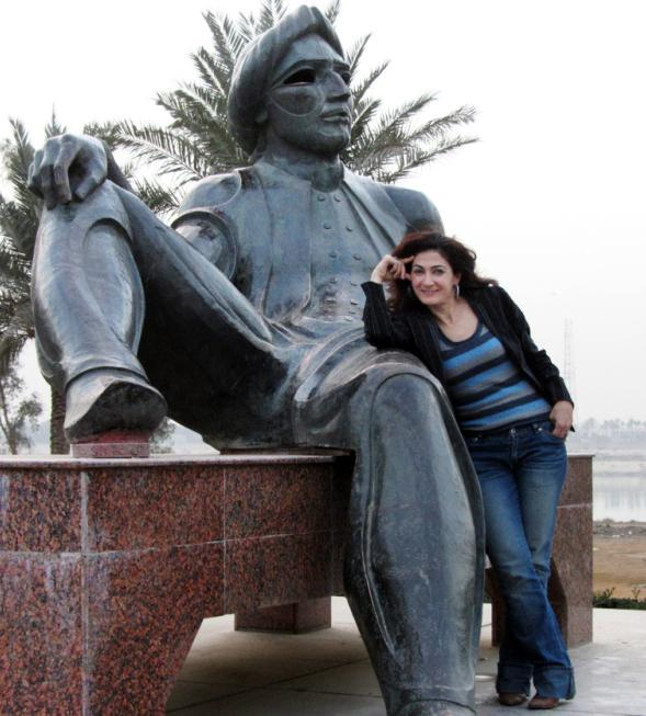 After a 20-year absence, Aseel Albanna returned to her native Iraq and found a very different country. Here, she poses with the statue of King Shahryar, a character in <em>The Thousand and One Nights</em>, near the Tigris River in Baghdad. The area used to be extremely popular, but many of the fish restaurants that once lined the streets have been torn down.