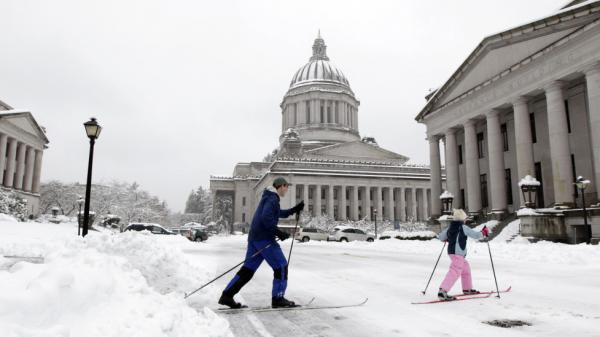 Amelia McHugh, 9, right, and her father, Noel McHugh, left, cross-country ski, in front of the Capitol in Olympia, Wash., on Wednesday.